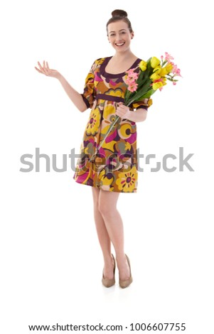 Happy young woman posing in summer dress, holding a bouquet of flowers, looking at camera, smiling. Isolated on white.