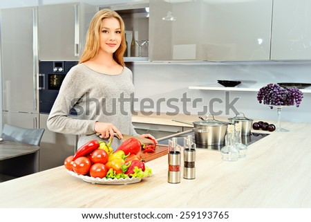 Happy young woman prepares healthy food in the kitchen. Healthy eating. Home interior. - stock photo