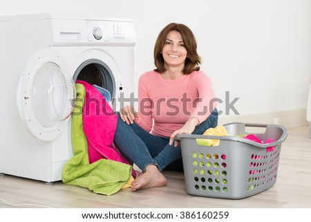 Happy Young Woman Putting Clothes Into Washing Machine At Home