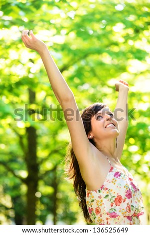 Happy young woman raising arms enjoying freshness of spring season in nature park surrounded by tress. Caucasian beautiful girl with open arms relaxing and celebrating life outdoors. - stock photo