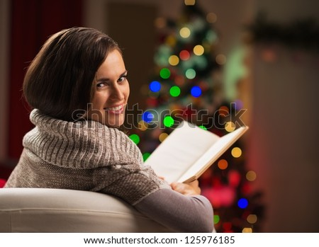 Happy young woman reading book in front of Christmas tree - stock photo