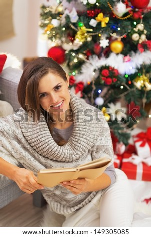 Happy young woman reading book near christmas tree - stock photo