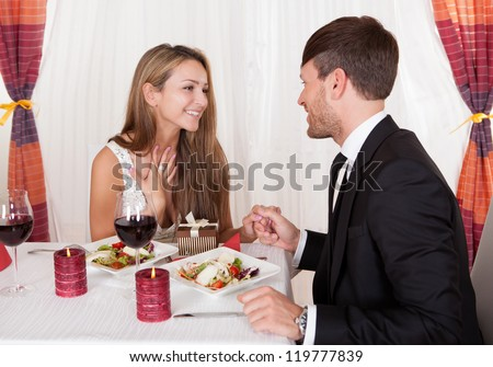 Happy young woman receives a gift from her partner. Romantic dinner setting with young couple dressed in evening wear - stock photo