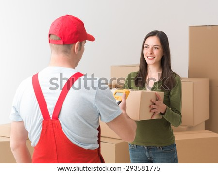 happy young woman receiving a parcel delivered by courier - stock photo