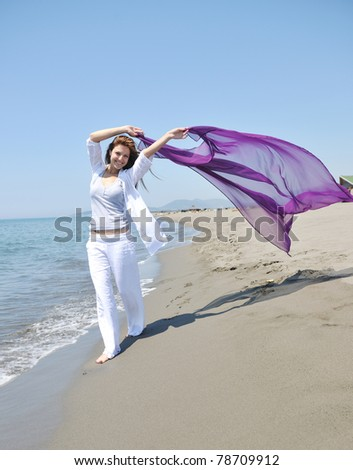 happy young woman relax on beautiful  beach at fresh summer morning and enjoy first ray of sun - stock photo