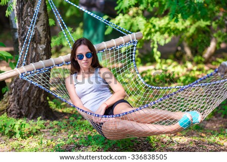 Happy young woman relaxing in hammock - stock photo