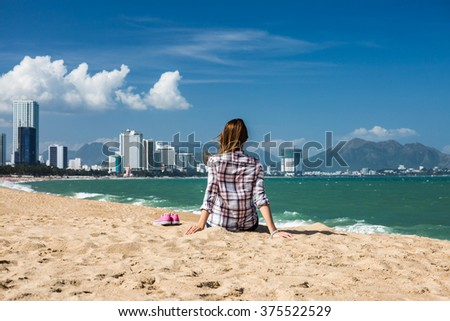 Happy young woman relaxing on the beach away from big city - stock photo