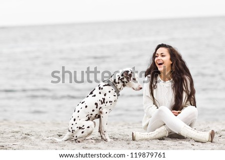 Happy young woman resting at beach in autumn with dog - stock photo