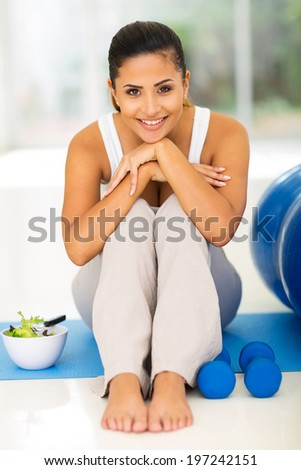 happy young woman resting on mat after exercise at home - stock photo