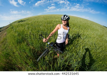 Happy Young Woman riding bicycle outside against blue sky. Healthy Lifestyle.