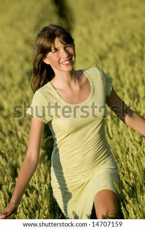 Happy young woman run in field.