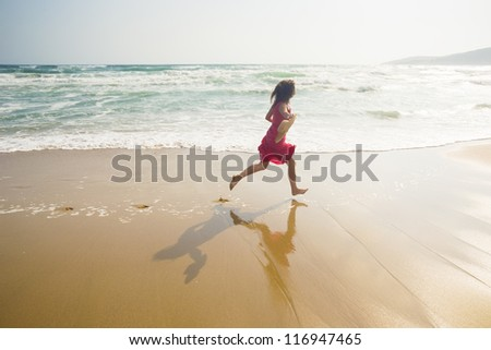 Happy young woman running along the beach - stock photo