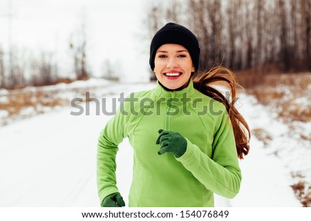 Happy young woman running in winter - stock photo