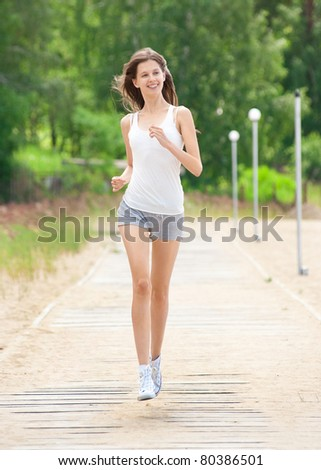 Happy young woman running outdoors in park - stock photo