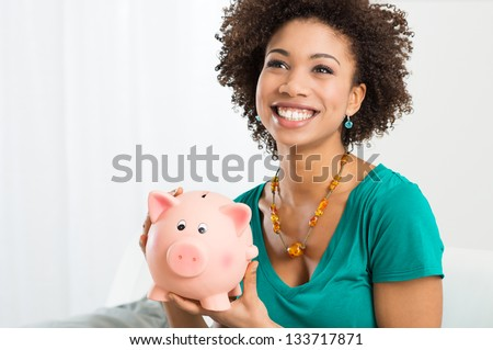 Happy Young Woman Saves Money in Piggy bank - stock photo
