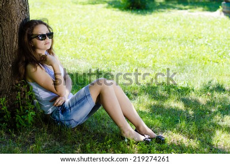 Happy young woman school girl sitting at tree in park on summer day