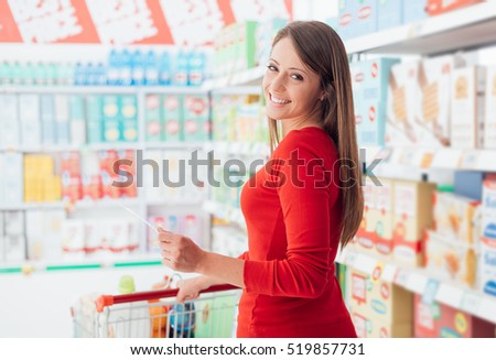 Happy young woman shopping at the grocery store, she is holding a list and pushing a cart, lifestyle and retail concept