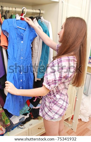 Happy young woman shopping for clothes at the mall , selecting a dress - stock photo