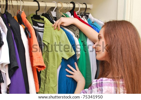 Happy young woman shopping for clothes at the mall , selecting a dress