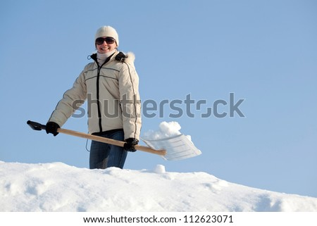 Happy young woman shovelling snow on a roof against blue sky
