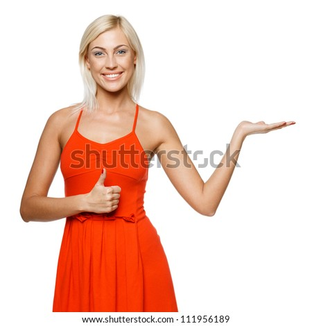 Happy young woman showing a product - empty copy space on the open hand palm, showing thumb up sign, over white background