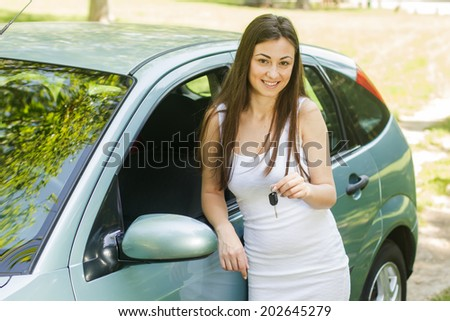 Happy young woman showing keys of new car. - stock photo
