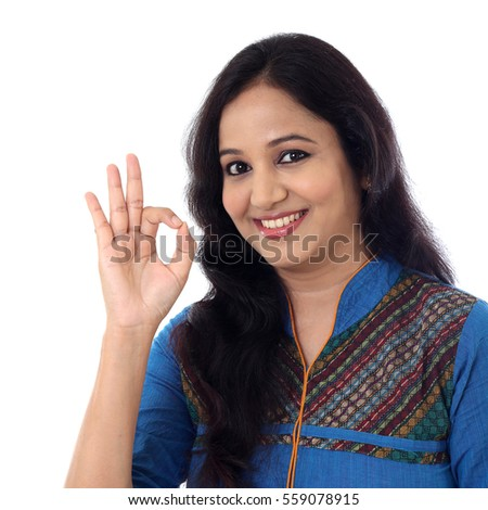 Happy young woman showing OK gesture against a white background