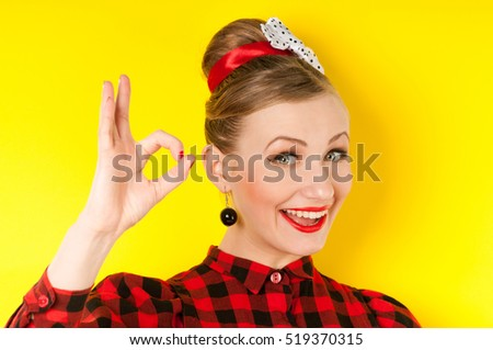 happy young woman showing ok sign with fingers an winking isolated on a yellow background stock photo
