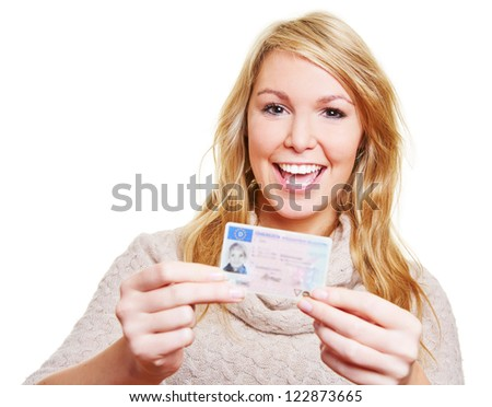 Happy young woman showing proudly her new driving licence - stock photo
