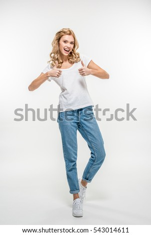 Happy young woman showing thumbs up isolated on white
