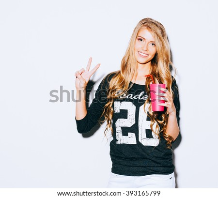 Happy Young Woman Showing Victory Sign and holding a pink glass with straw in hand On White Background. Indoor. Warm color. Hipster. - stock photo