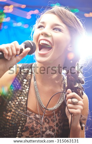 Happy young woman singing in mike - stock photo
