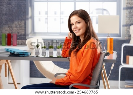 Happy young woman sitting at home, smiling in orange pullover. - stock photo