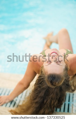 Happy young woman sitting at poolside - stock photo
