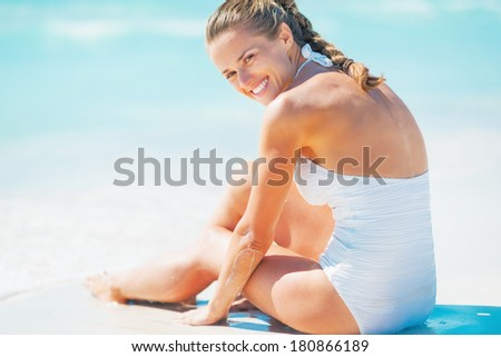 Happy young woman sitting at seaside - stock photo