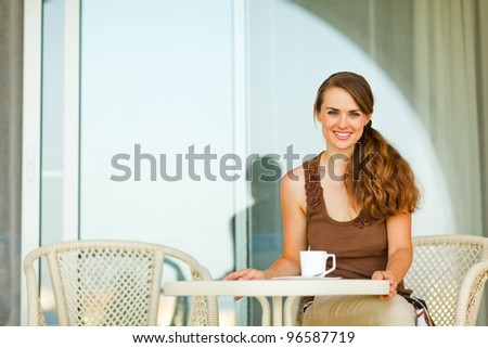 Happy young woman sitting at terrace with cup of tea