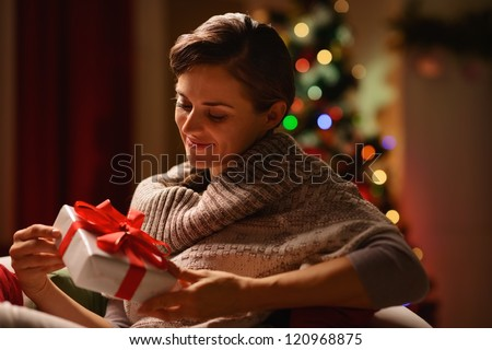 Happy young woman sitting chair with Christmas present box - stock photo
