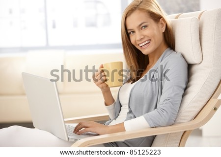 Happy young woman sitting in armchair with laptop computer, holding coffee mug, laughing, looking at camera.? - stock photo