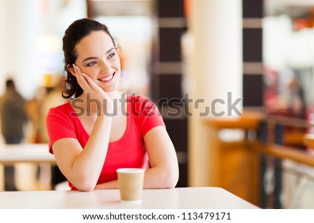 happy young woman sitting in coffee shop - stock photo