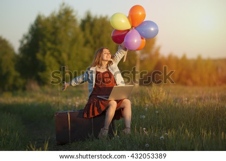 Happy young woman sitting on big suitcase holding colorful balloons on the meadow. Online shopping in travel, communication, freedom and enjoy - stock photo