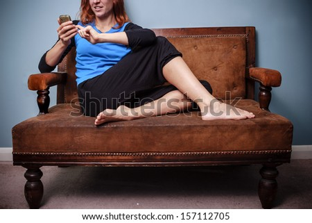 Happy young woman sitting on old sofa using her phone - stock photo
