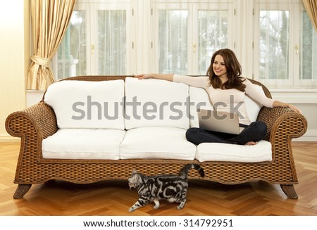Happy young woman sitting on sofa with laptop and a cat walks in front of her - stock photo