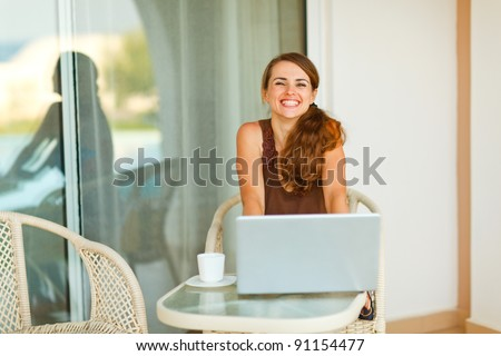 Happy young woman sitting on terrace with cup of coffee and laptop