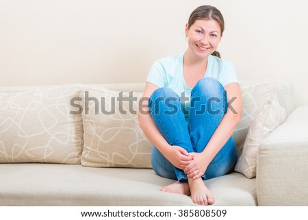Happy young woman sitting on the couch resting - stock photo