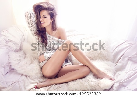 Happy young woman sitting on the white couch with her beautiful legs crossed - stock photo