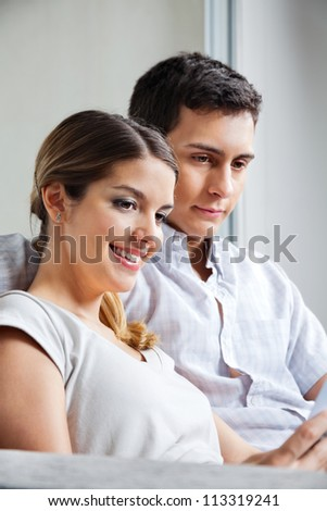 Happy young woman sitting with boyfriend