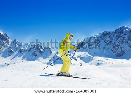 Happy young woman ski in the mountain with high rocky peaks behind her