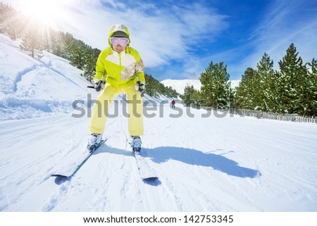 Happy young woman skier in bright clothes going downhill - stock photo