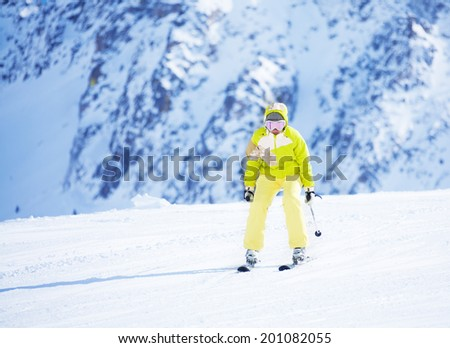 Happy young woman skier in bright clothes going downhill with mountain wall on background - stock photo