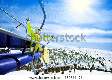 Happy young woman skier sit on ski lift chair, smiling and cheerfully lifting her hands - stock photo